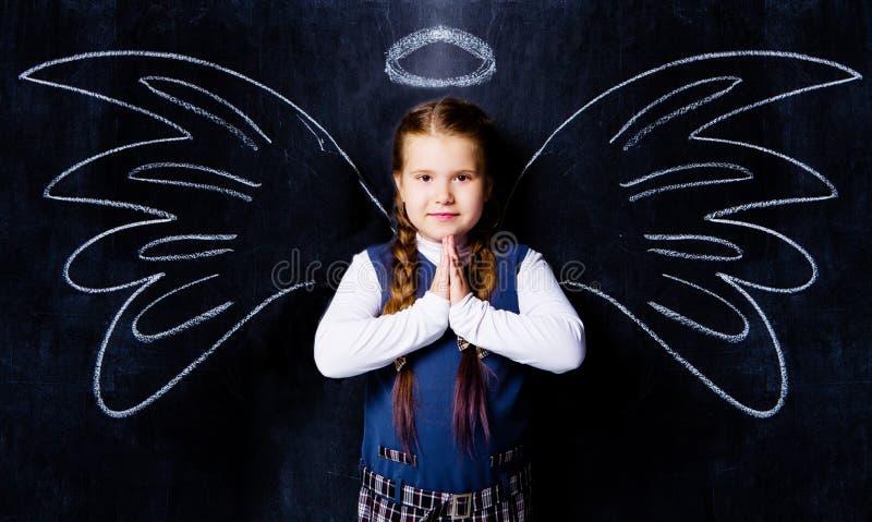 反对黑板的女小学生,有拉长的天使的飞过 库存照片