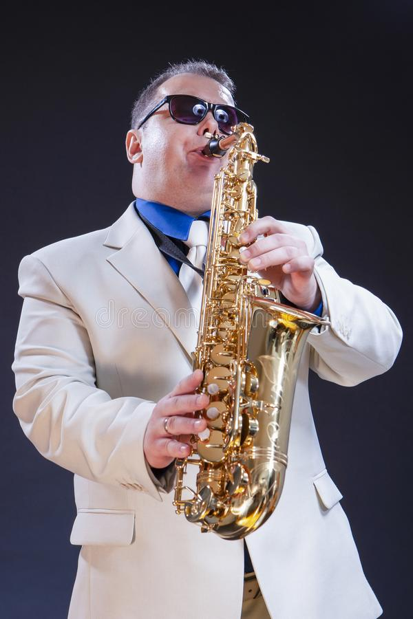 反对黑背景的白种人成熟使用的萨克斯管吹奏者 免版税库存图片
