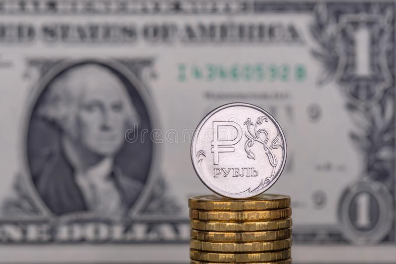 反对1一美元钞票背景的一卢布硬币  库存照片