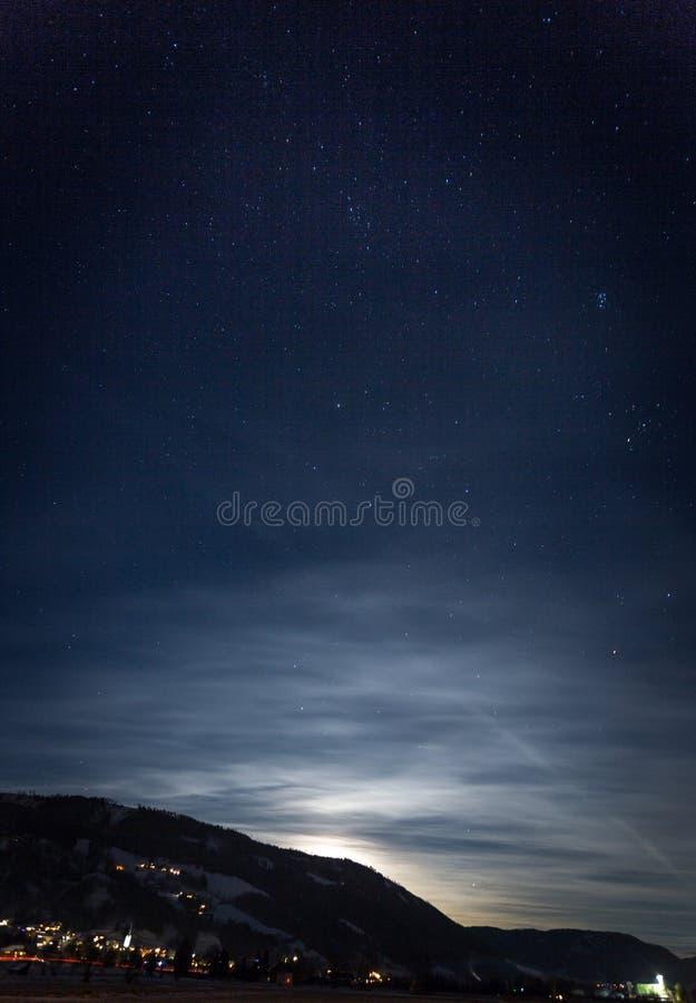 反对满天星斗的在附近的天空和光亮的月亮的山剪影 库存照片