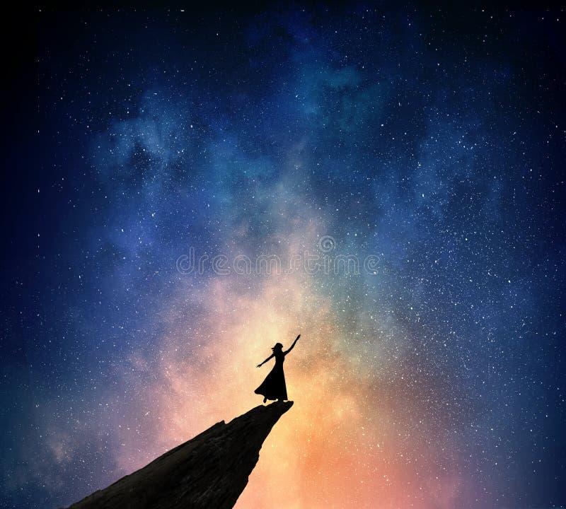 反对满天星斗的天空的妇女 混合画法 库存照片
