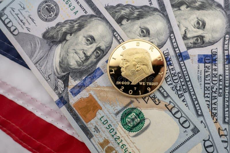 反对$100张票据和美国旗子背景的唐纳德・川普硬币  免版税图库摄影