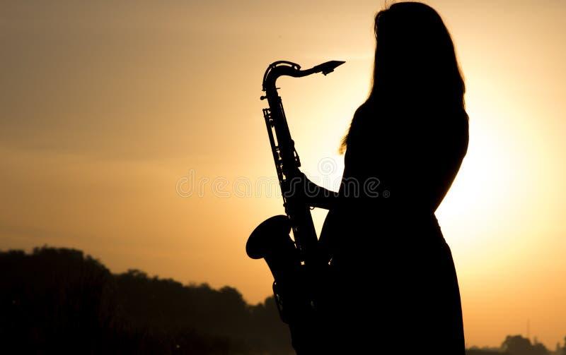 反对黎明的女性剪影与一支萨克斯管在他的手上 免版税库存图片
