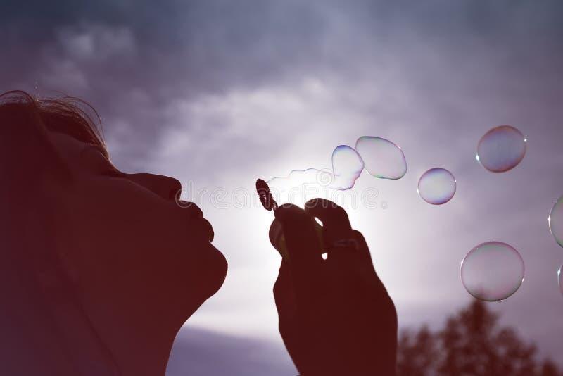 反对晴朗的蓝天的妇女吹的泡影的剪影的看法的低角度关闭 库存照片