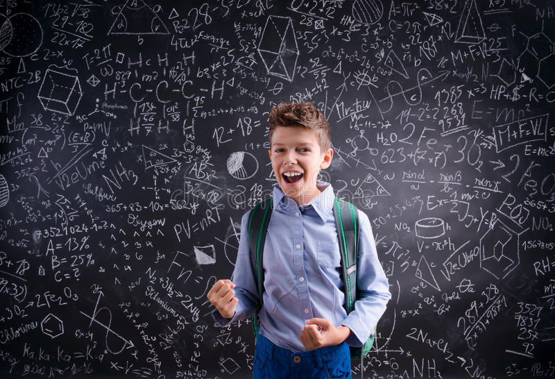 反对黑板的激动和战胜男孩有数学的 库存照片