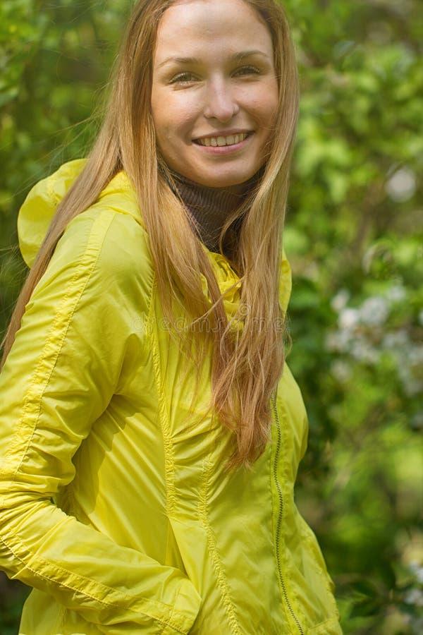 反对绿色公园的微笑的女孩 库存图片