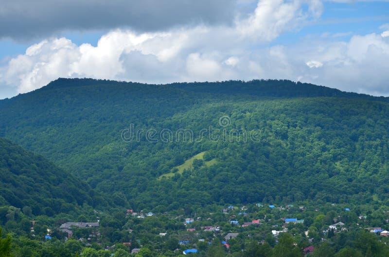 反对绿色山背景的村庄  美好的r 免版税库存照片