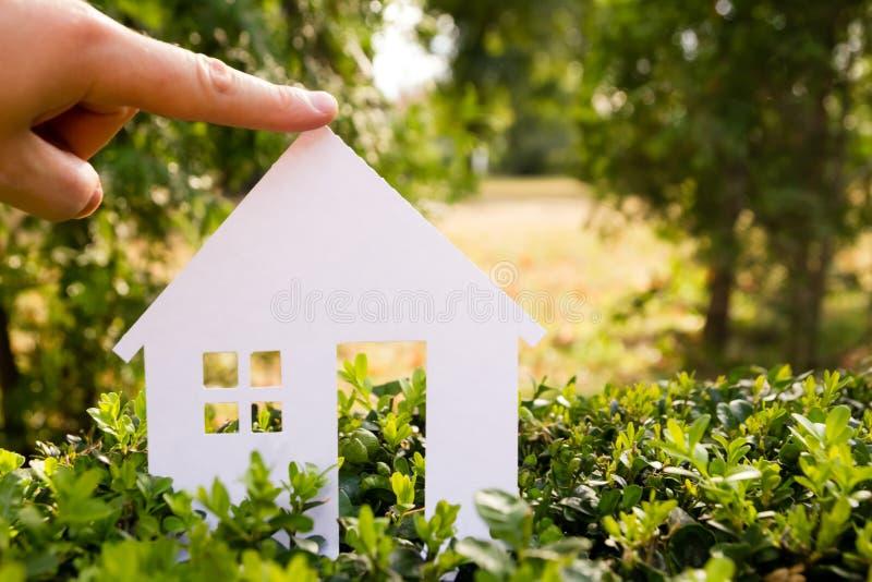 反对绿色背景的纸房子 实际概念的庄园 库存图片