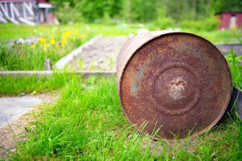 反对绿草的老生锈的桶 免版税图库摄影