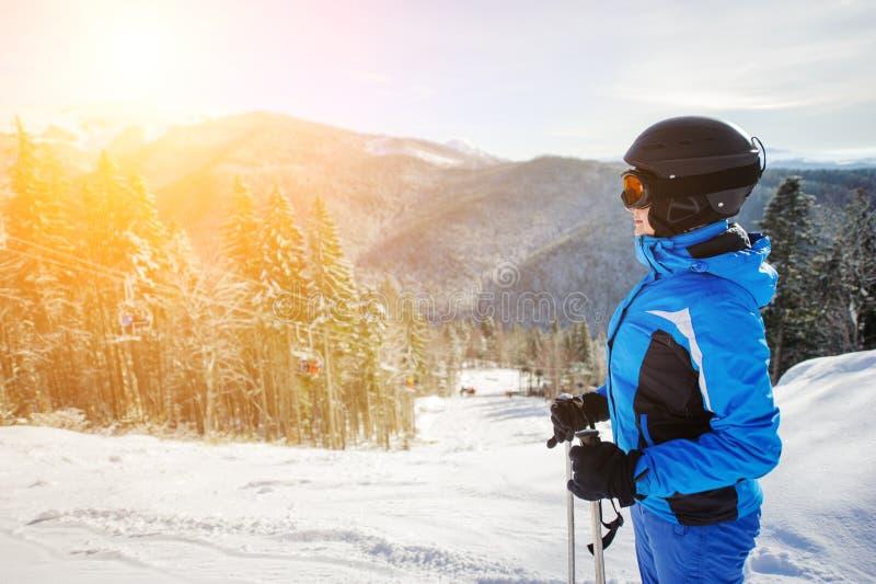 反对滑雪电缆车和冬天山背景的年轻女性滑雪者 免版税库存图片