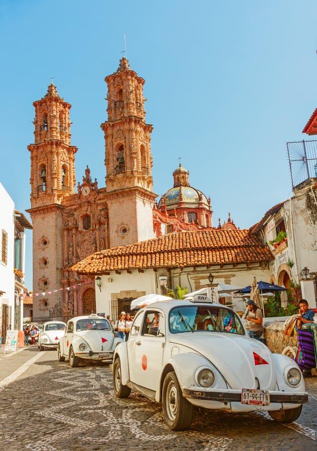 反对Taxco,墨西哥大教堂的微型出租汽车  库存照片