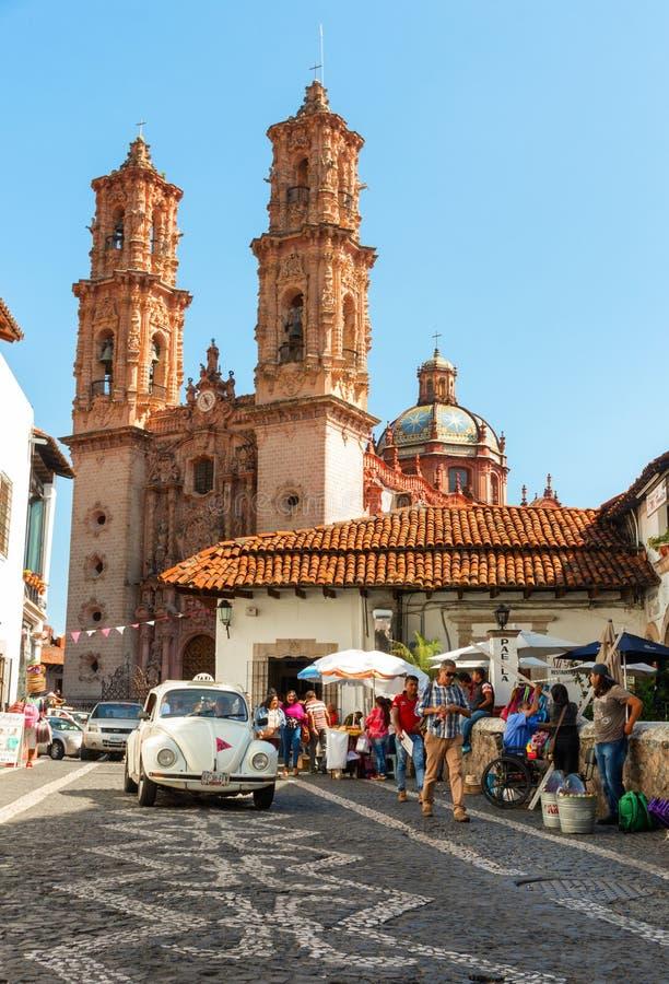 反对Taxco,墨西哥大教堂的微型出租汽车  图库摄影