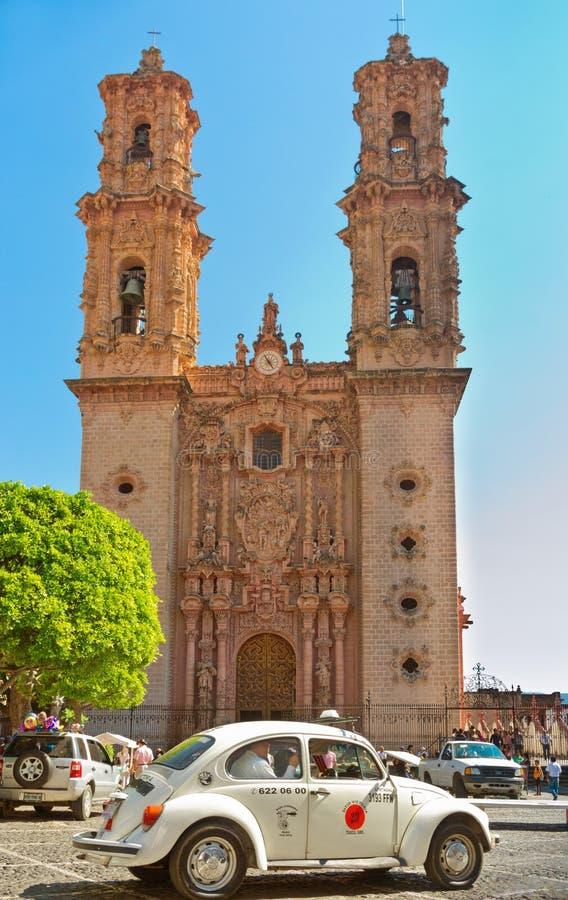 反对Taxco,墨西哥大教堂的微型出租汽车  免版税库存图片