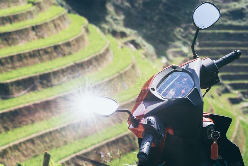反射在有Sapa米领域的摩托车镜子的太阳在背景,越南 免版税库存照片