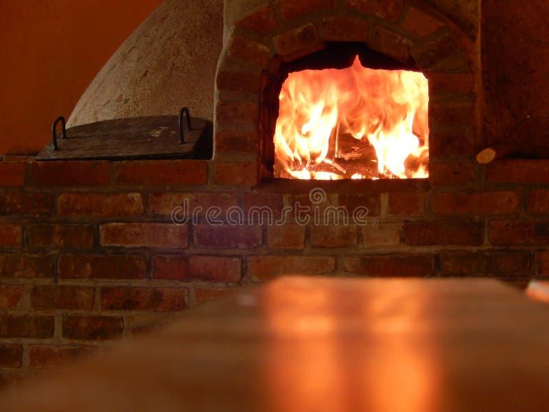 反射在桌上的木烤箱火 库存图片