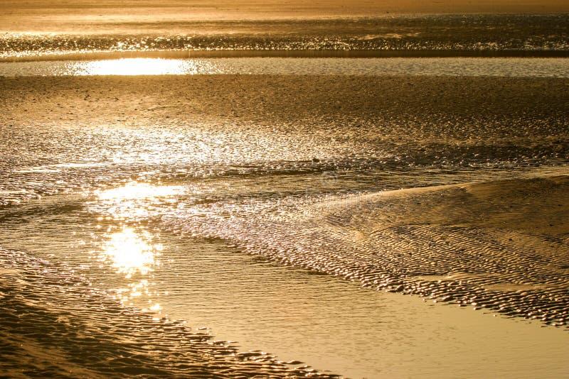反射在沙子海滩的日落 免版税库存照片
