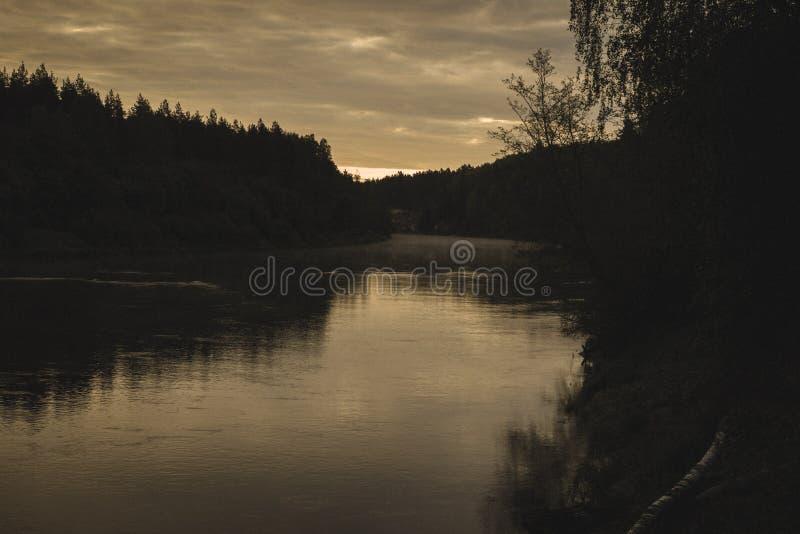 反射在河中高亚河镇静水的天空蔚蓝和云彩在拉脱维亚在秋天-葡萄酒减速火箭的神色 库存照片