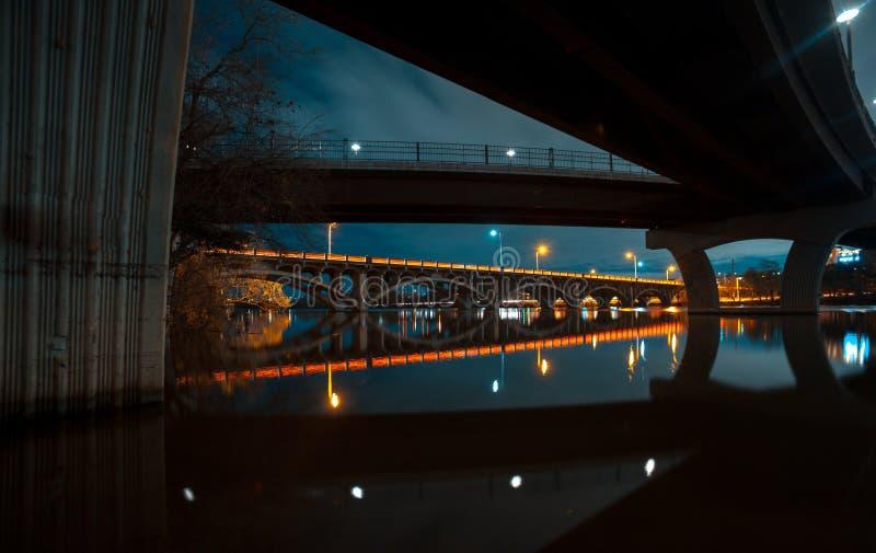 反射在湖的两座桥梁在夜wirh明亮的充满活力的反射和轻的足迹 免版税库存照片
