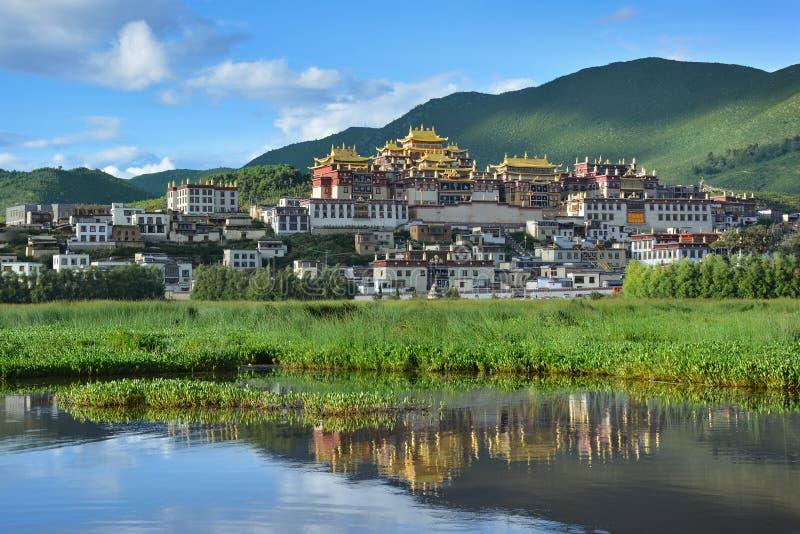 反射在湖的Ganden Songzanlin复合体 香格里拉,中国 图库摄影