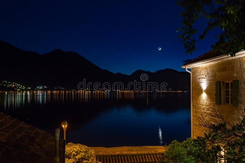 反射在科托尔海湾,黑山的晚上的月亮和星和电灯 库存照片