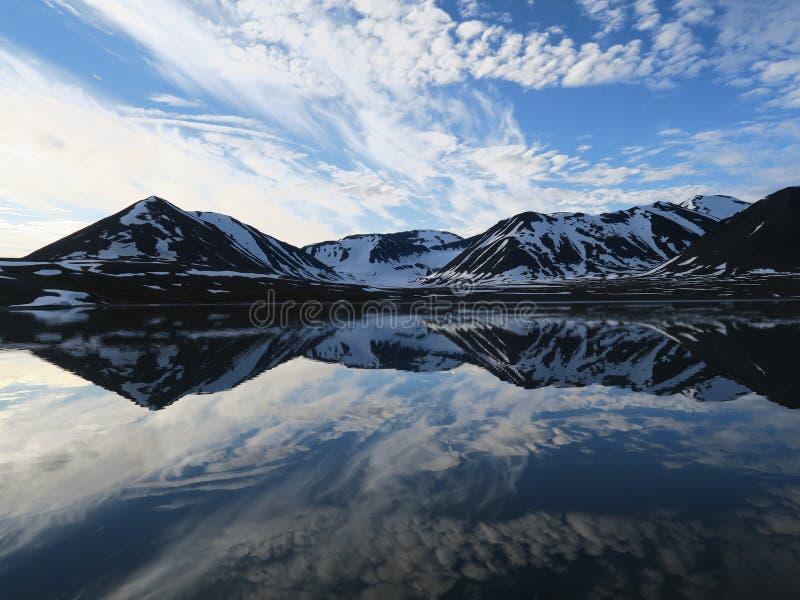 反射在镇静水域,斯瓦尔巴特群岛,挪威中的云彩 免版税图库摄影