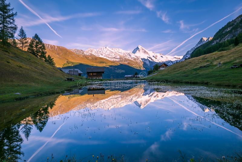 反射在Altitude湖的斯诺伊山和木瑞士山中的牧人小屋在S 库存照片