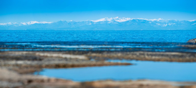 反射性天空蔚蓝在码头和snowly山的水中 免版税库存照片