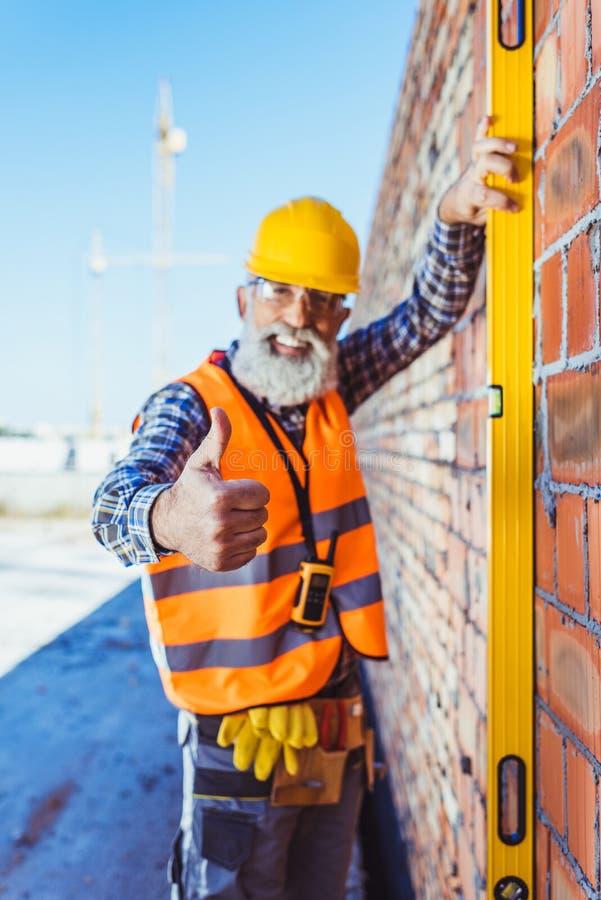 反射性拿着水平仪的背心和安全帽的微笑的工作者对墙壁和显示 免版税图库摄影