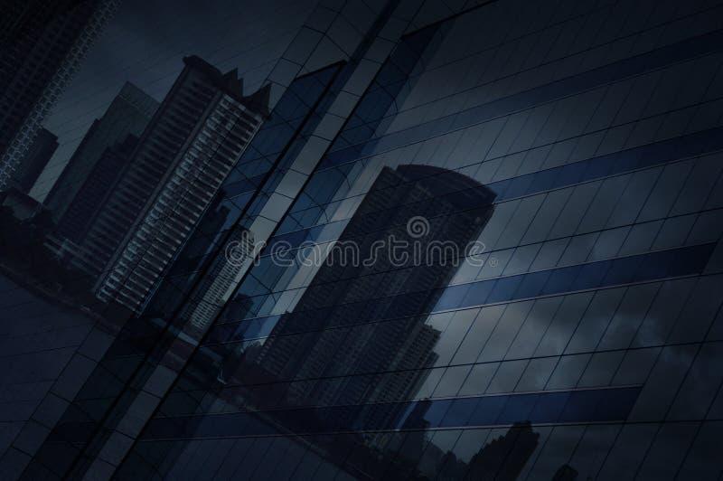 反射现代城市和黑暗的strom天空在玻璃窗塔 免版税库存照片