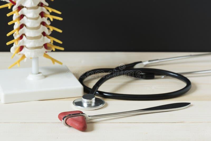 反射锤子、听诊器和脊椎在木桌上塑造 图库摄影