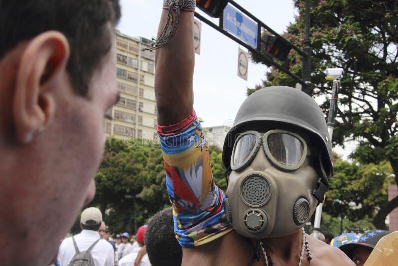 反尼古拉斯・马杜罗抗议者佩带毒气催泪面具在把变成暴乱在加拉加斯,委内瑞拉的群众游行期间 图库摄影