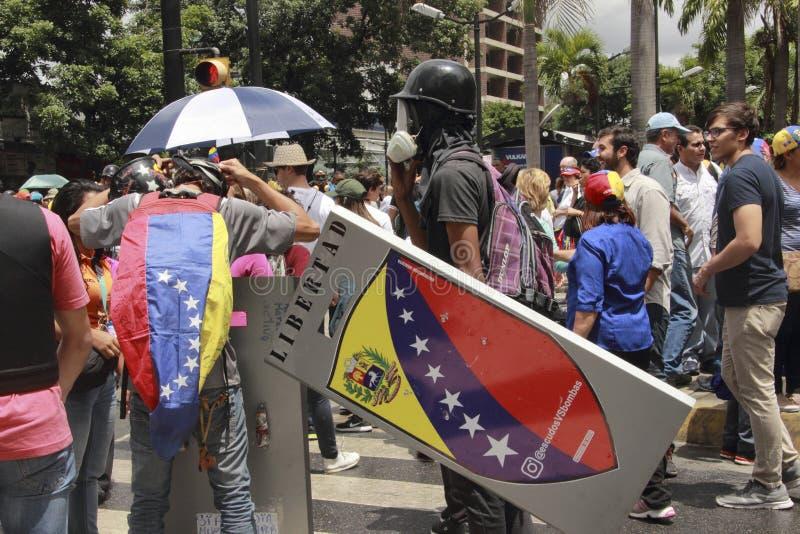反尼古拉斯・马杜罗抗议者佩带毒气催泪面具在把变成暴乱在加拉加斯,委内瑞拉的群众游行期间 库存照片
