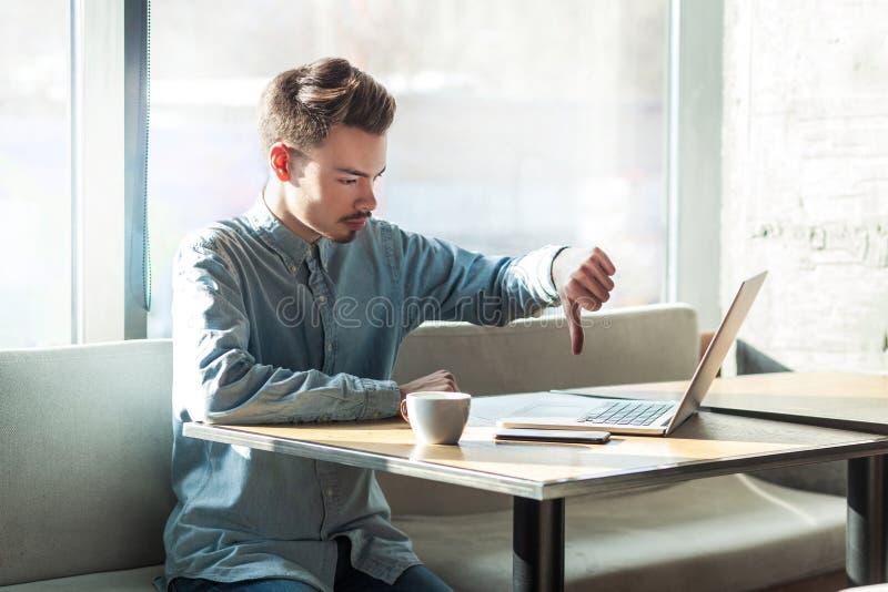 反感!消极蓝色衬衣的批评有胡子的年轻自由职业者侧视图画象在咖啡馆坐并且打视频通话 库存照片
