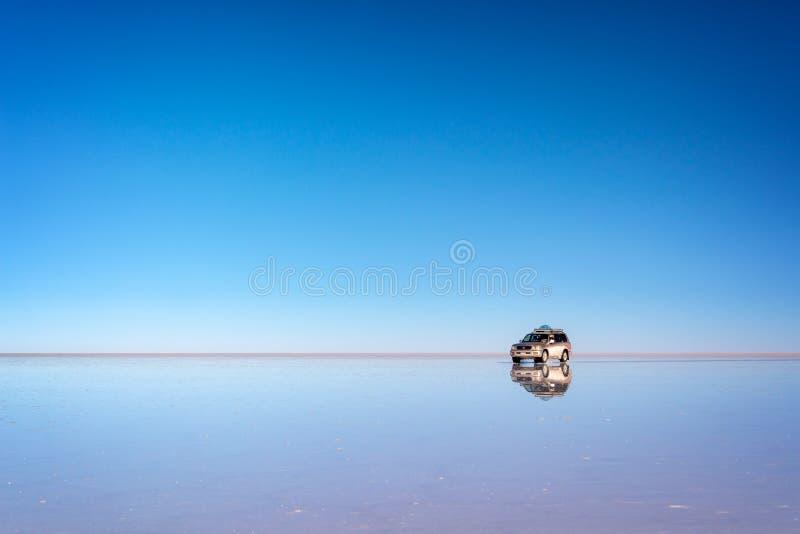 反映一辆4x4汽车,波托西,玻利维亚的作用和反射在撒拉族de Uyuni Uyuni盐舱内甲板的 免版税库存图片