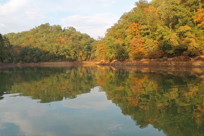 反映在山湖的秋叶和天空 免版税库存图片