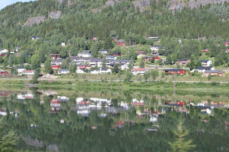反映山,在湖水的村庄看法在旅行期间 库存图片