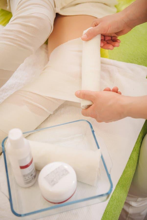 反脂肪团包裹腿的做法在温泉中心 免版税库存图片