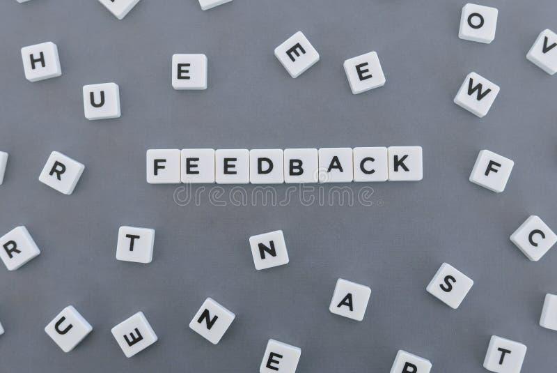 反馈词由方形的信件词制成在灰色背景 库存照片