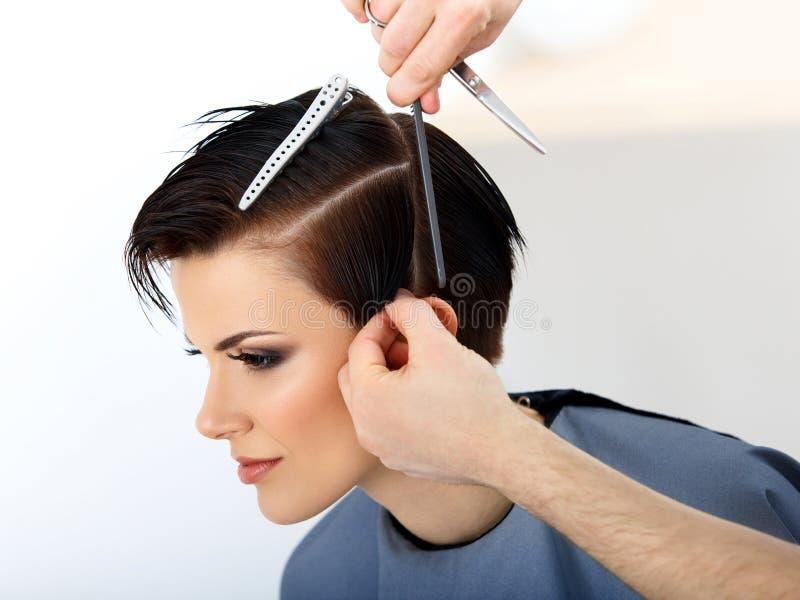 头发。美发师切口在美容院的妇女头发。 免版税图库摄影