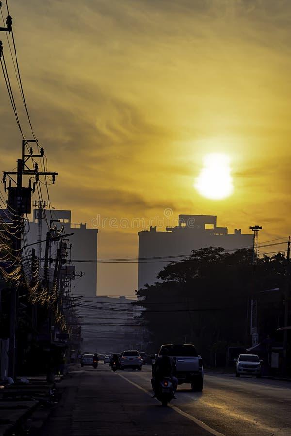 发光在大厦和汽车的清早阳光在路在暖武里Bangyai在泰国 12月25日 免版税库存照片
