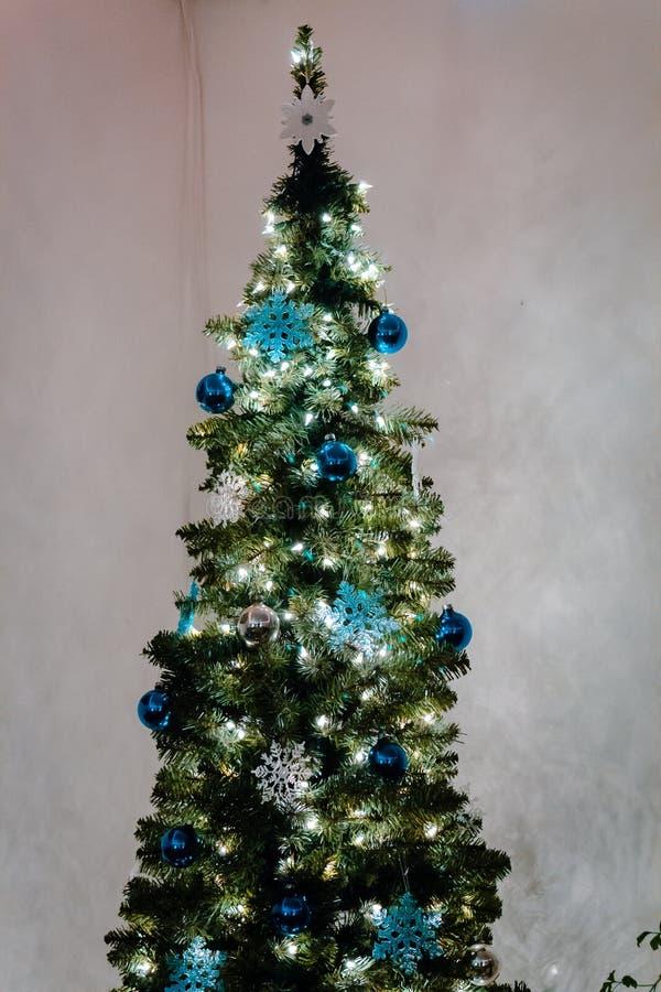 发光在屋子的角落的圣诞树 免版税库存图片