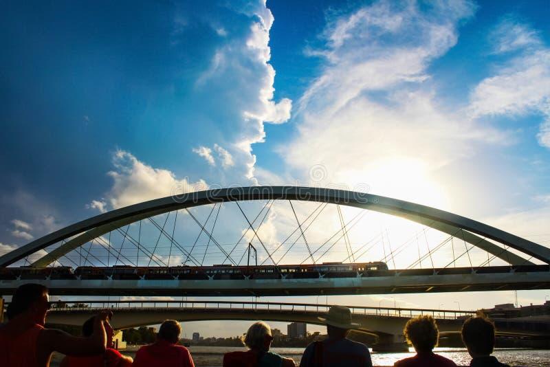 发光在火车的Cloudscape和太阳横渡有观看它从在前景的轮渡的人剪影的布里斯班河  免版税库存图片