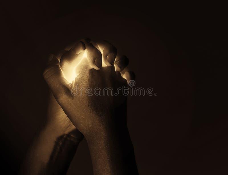 发光在祈祷的手上 库存图片