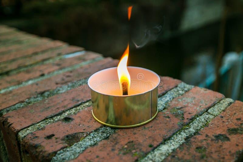发光在金属锡的蜡烛黄色,红色和橙色火焰 免版税库存图片