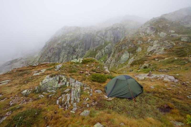 发光由阳光的高山谷 绿色帐篷在牧场地 受欢迎的旅游胜地 与帐篷的剧烈和美丽如画的场面 库存照片