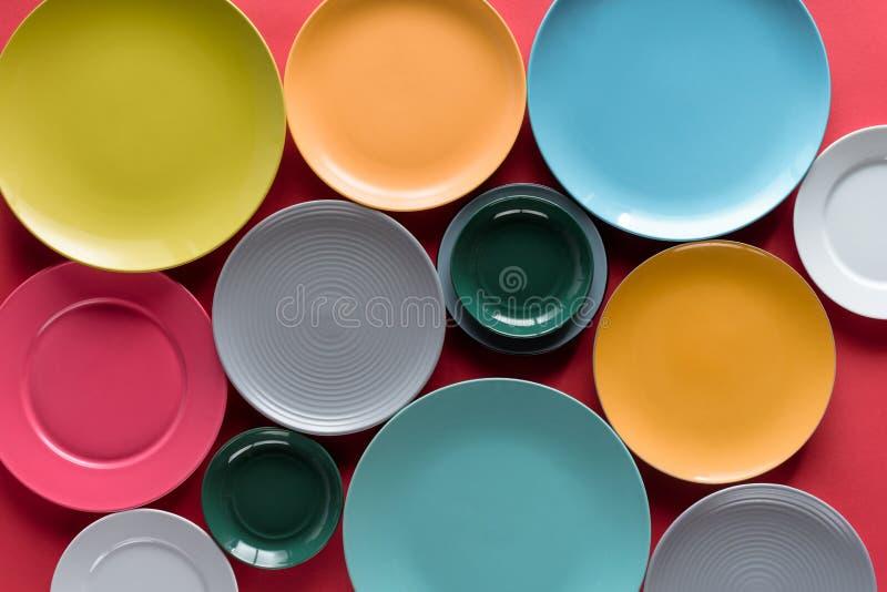 发光的五颜六色的在红色背景的厨房陶瓷板材 免版税库存照片