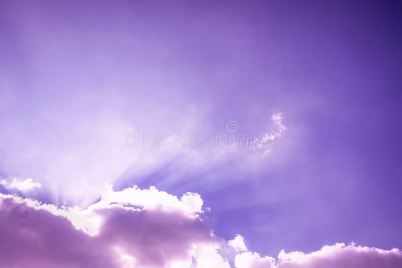 发光的光  光柱和蓬松云彩 与太阳光芒的桃红色紫色天空 免版税库存图片