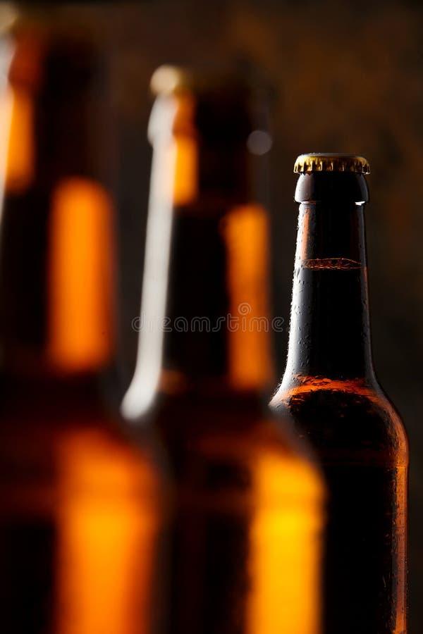 发光的啤酒瓶在客栈的黑暗中 免版税库存照片