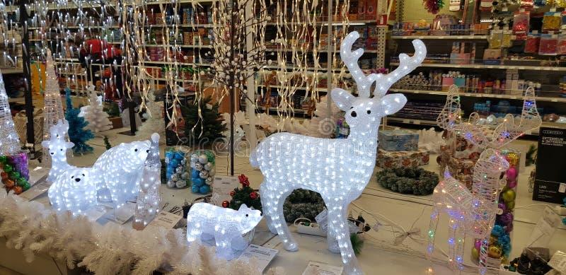 发光的圣诞节鹿和其他装饰在商店 免版税库存图片