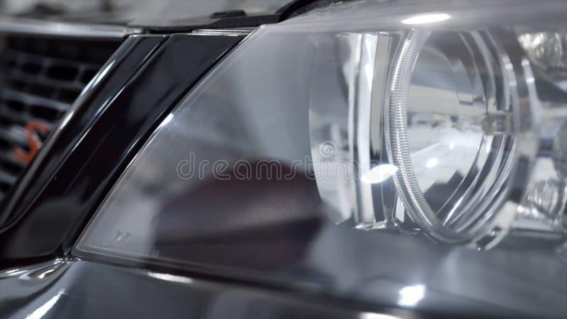 发光的新的汽车车灯特写镜头  r 有准备好黑新的汽车反射和亮光的干净的车灯买 库存图片